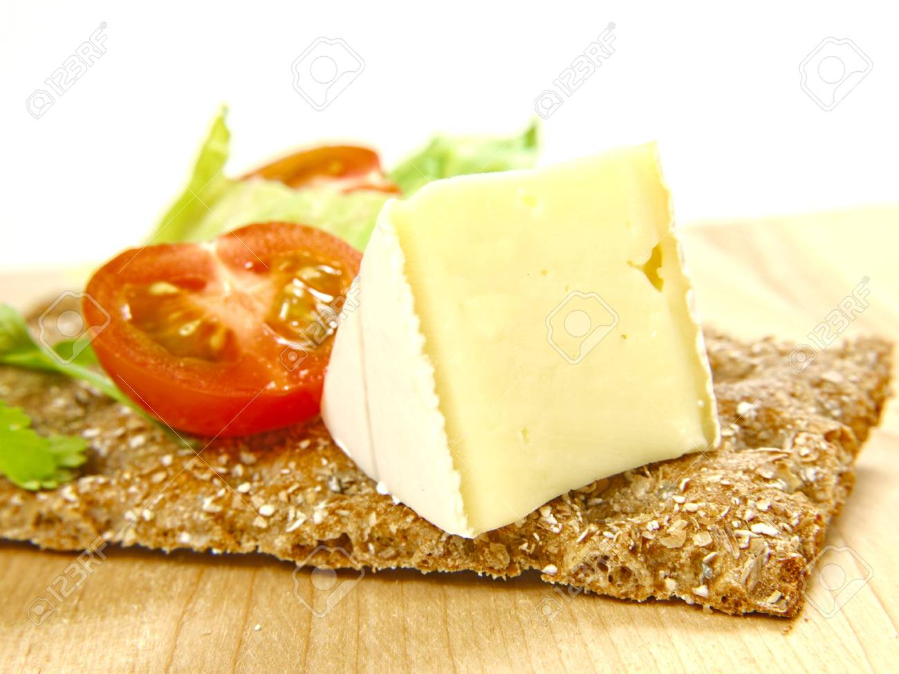 Cracker on wooden board, with soft cheese and tomato Stock Photo - 13107152