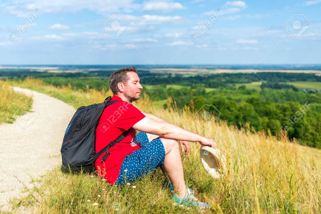 Traveler male relaxing meditation with serene view mountains forest landscape summer day. Man enjoying a view from the top of mountain. Relaxing middle age man alone with nature.Closeup,side view. - 172593469