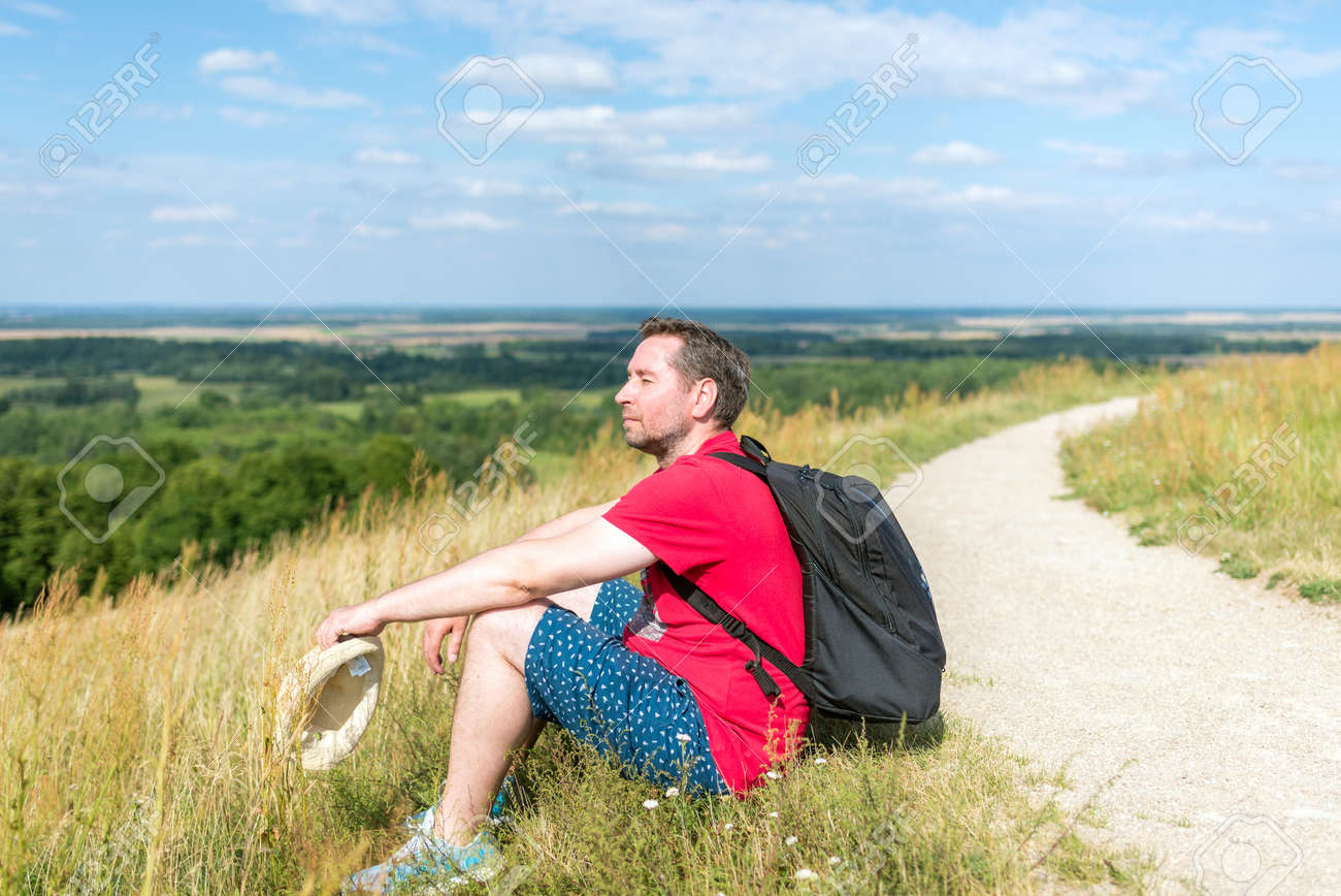 Traveler male relaxing meditation with serene view mountains forest landscape summer day. Man enjoying a view from the top of mountain. Relaxing middle age man alone with nature.Closeup,side view. - 172999994