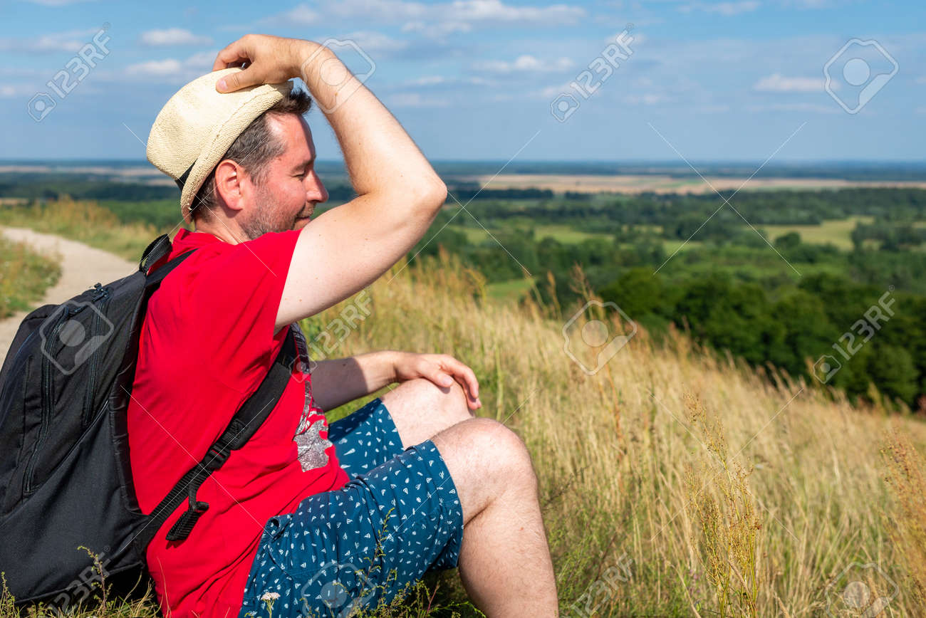 Traveler male relaxing meditation with serene view mountains forest landscape summer day. Man enjoying a view from the top of mountain. Relaxing middle age man alone with nature.Closeup,side view. - 173000563