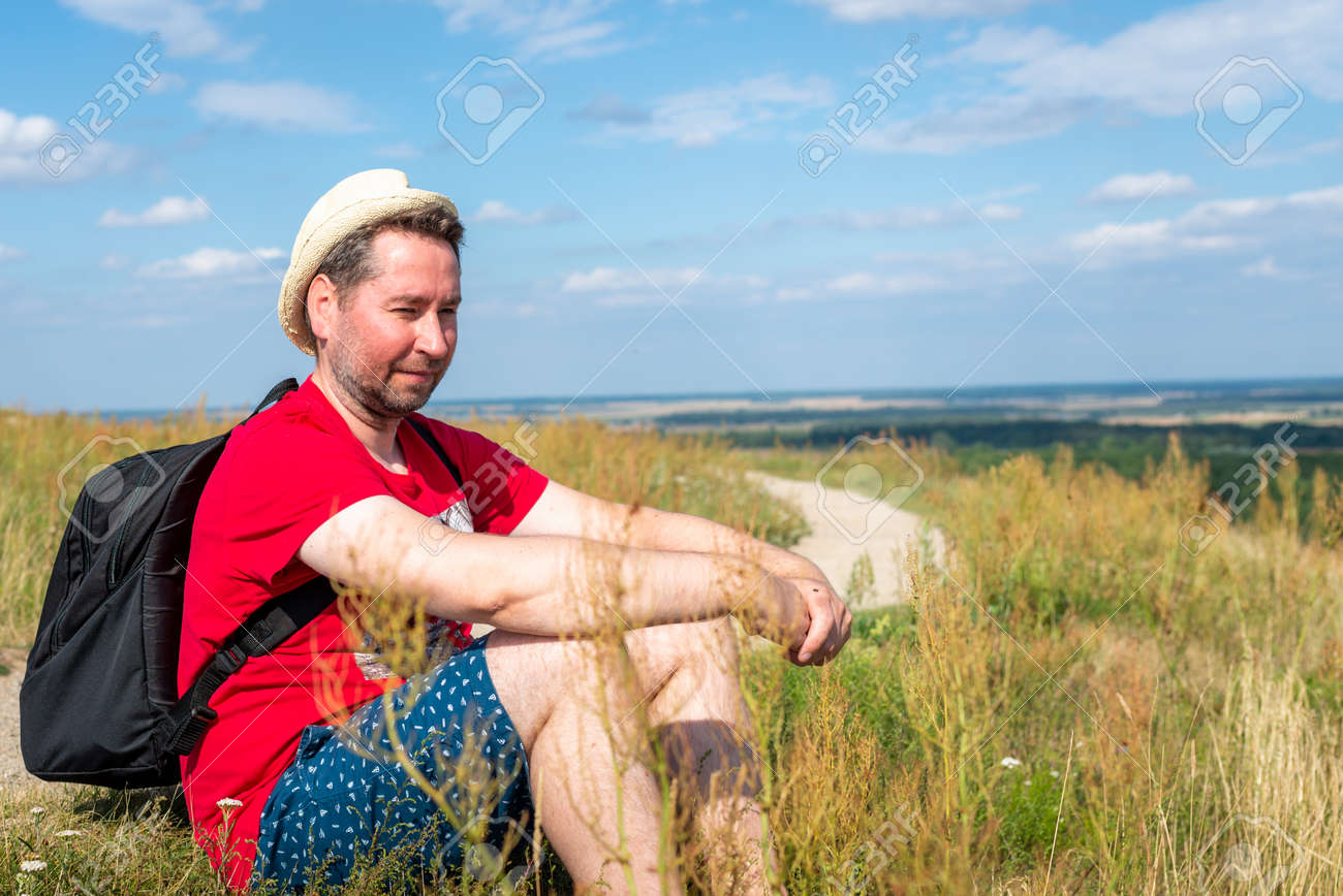 Traveler male relaxing meditation with serene view mountains forest landscape summer day. Man enjoying a view from the top of mountain. Relaxing middle age man alone with nature.Closeup,side view. - 173687546