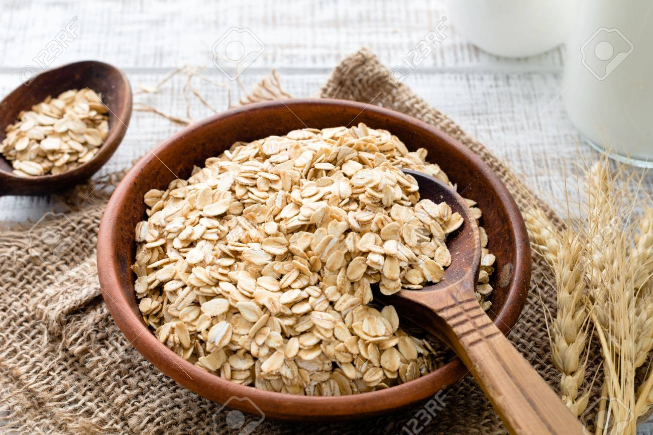 Rolled oats or oat flakes in bowl with wooden spoons golden stock rolled oats or oat flakes in bowl with wooden spoons golden wheat ears and bottle ccuart Image collections