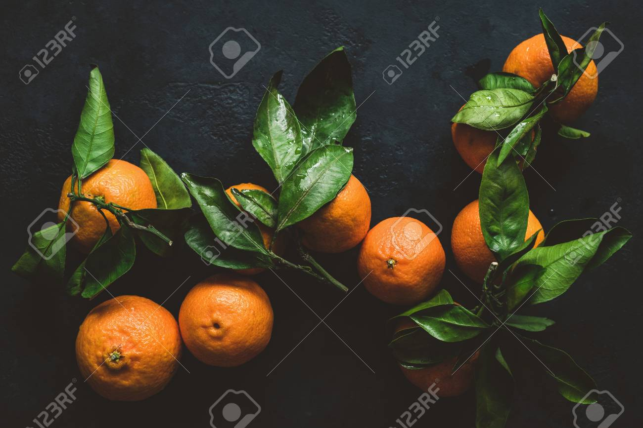 Tangerines or clementines with green leaf. Still life on dark background. Top view, toned image Stock Photo - 92620743