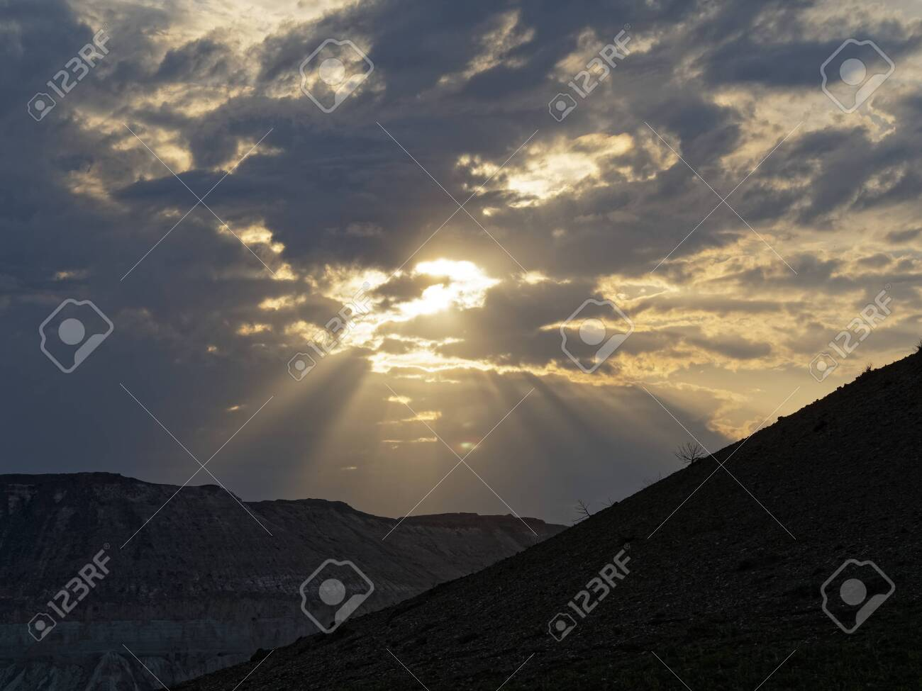 Disturbing sky in the mountains of Kazakhstan. The sun's rays make their way through the clouds in the mountains of Kazakhstan. - 131608076