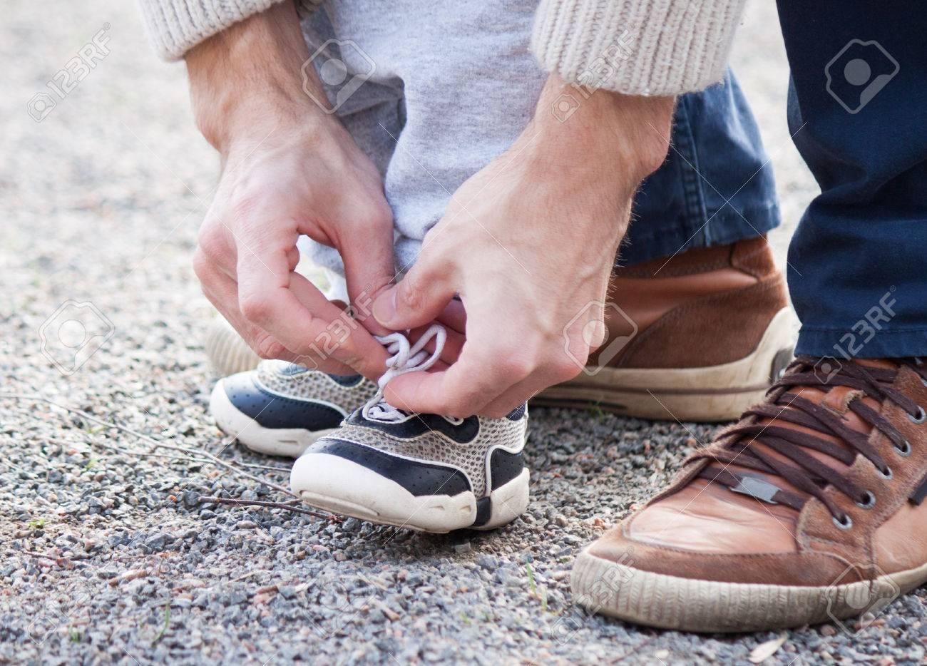 Dad tying the laces on a child sneakers - 55042598