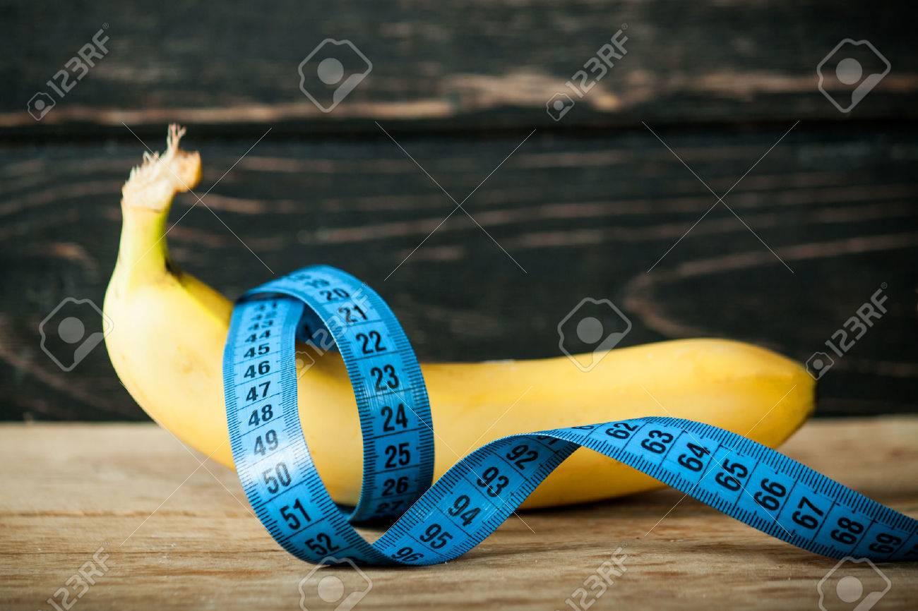 Fresh banana and measuring tape on wood desk - 70276195