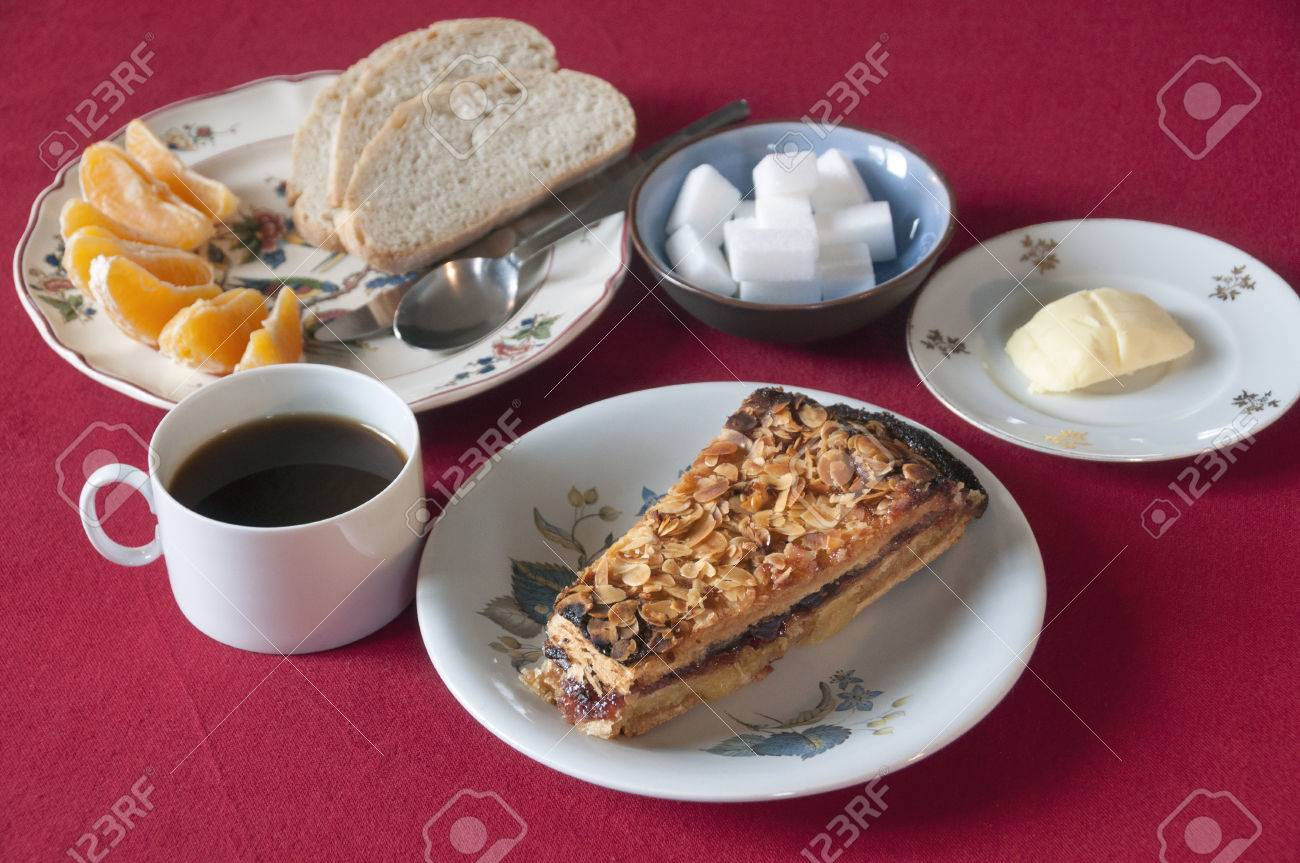 Breakfast set with coffee cake bread butter and orange wedges - 40500468