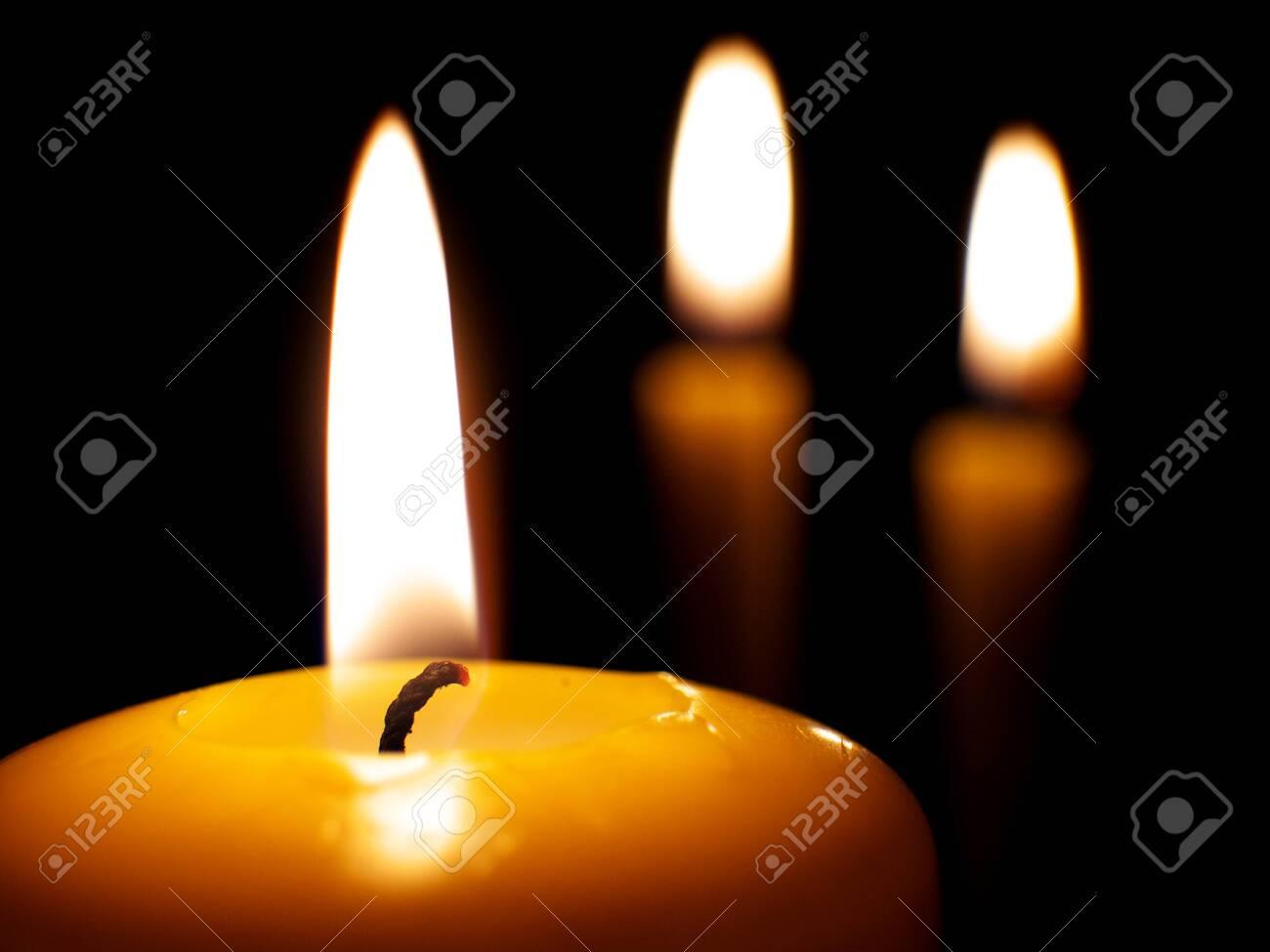 yellow burning candles on dark background, macro - 152881090