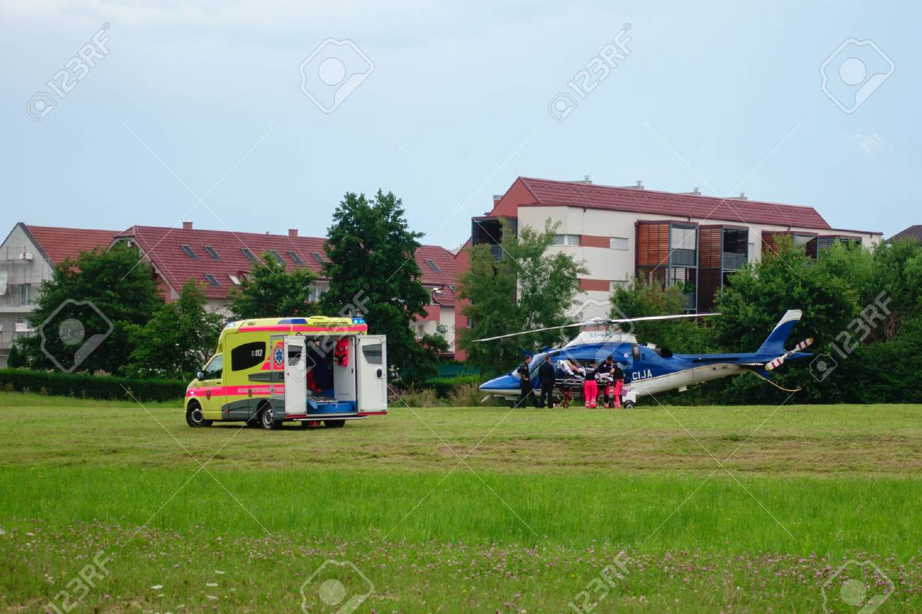 Slovenska Bistrica, July 21 2018: Paramedics hand over patient to Police helicopter for emergency aerial transport to hospital. Ambulance car with flashing lights. Live news. - 109779189