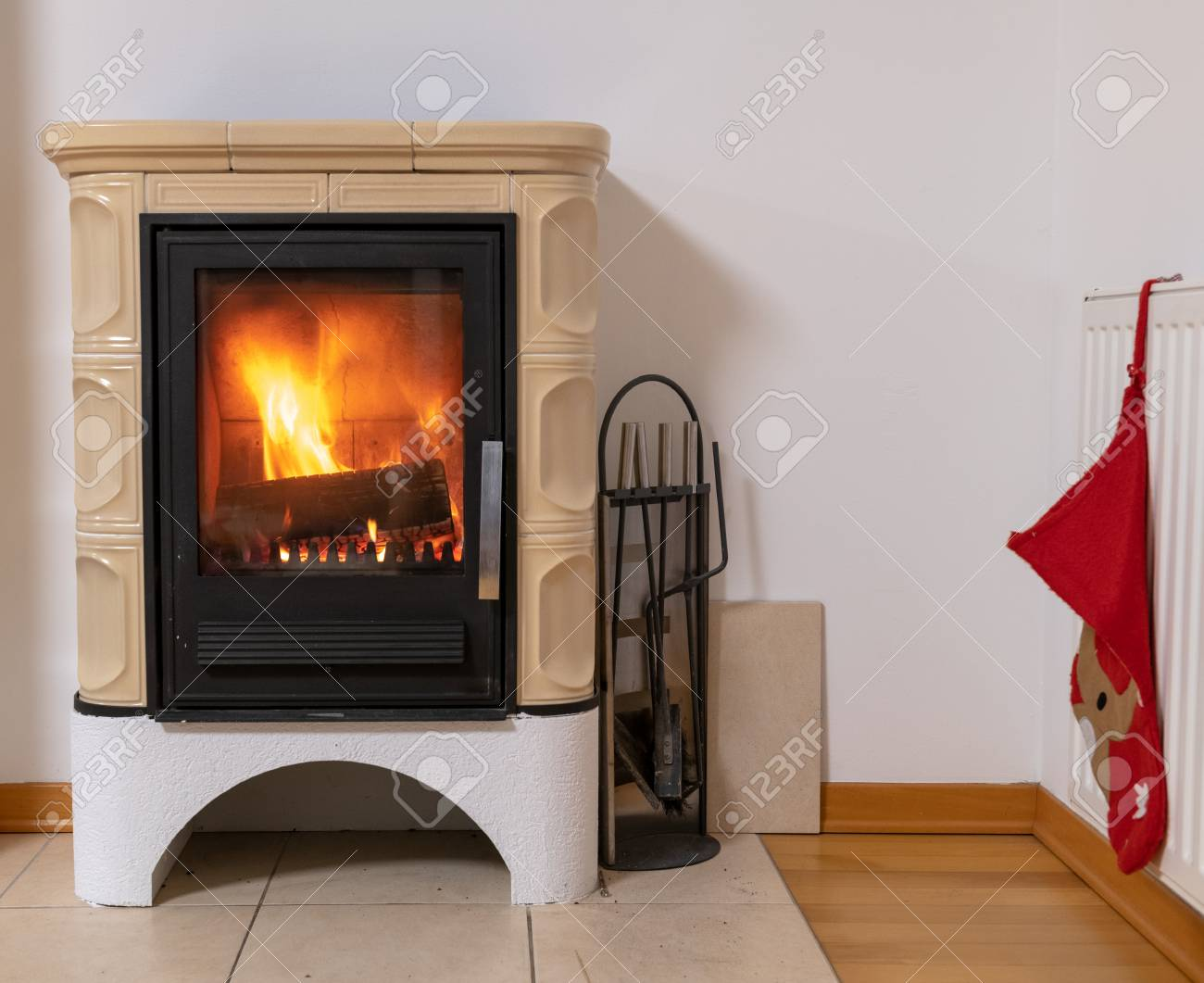 Tiled stove with fire burning inside, cosy and warm interior scene, heating in winter, Christmas decoration on the wall - 120368011