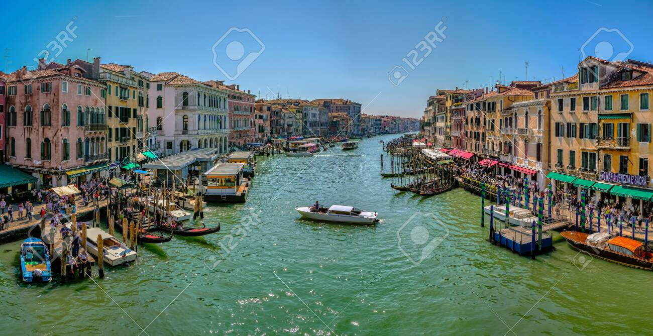 Venice, Italy - April 17 2019: Canale Grande, the Grand Canal in Venice, Italy from the Rialto bridge with gondoals, boats and dense water traffic, tourists walking on shore and sitting in cafes - 137009121