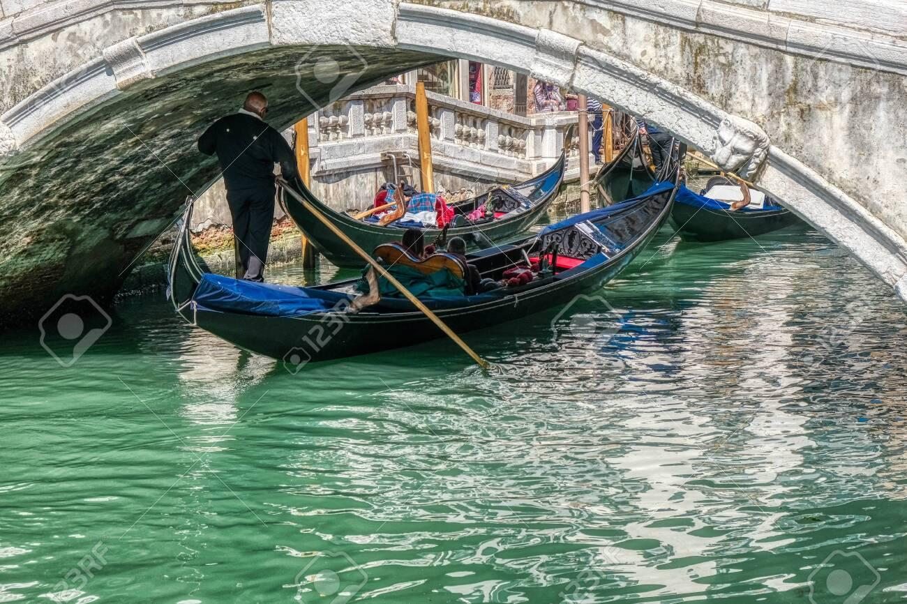 Venice, Italy - April 17 2019: Gondola passing below one of many bridges in Venice, Italy - 137009125