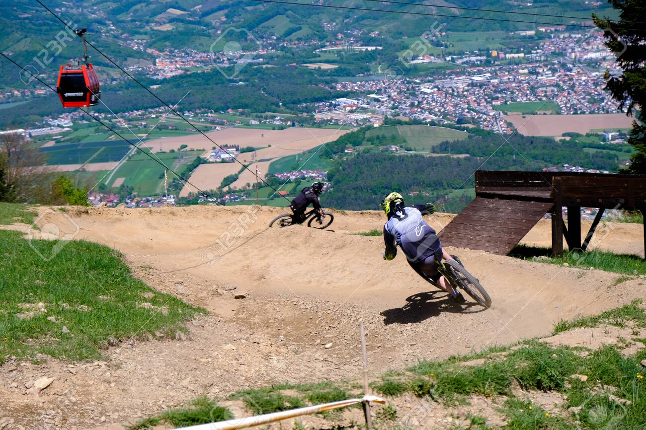 Maribor, Slovenia - May 2, 2019: Downhill mountain bikers riding down the trail on Pohorje near Maribor, Slovenia. Pohorje bike park is very popular with riders. - 137009422
