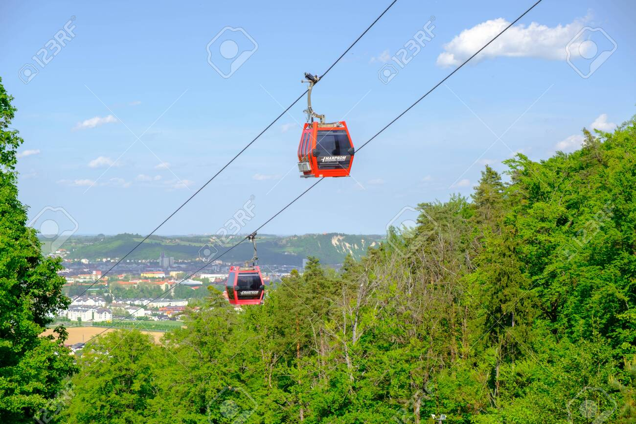 Maribor, Slovenia - May 2 2019: Red cabins of the Pohorska vzpenjaca cable car in Maribor, Slovenia connect the top of Pohorje mountain with the city - 137010534