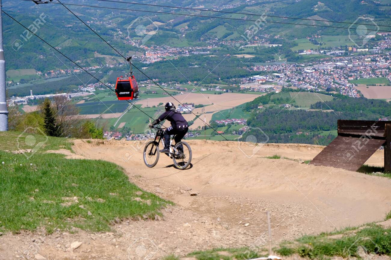 Maribor, Slovenia - May 2, 2019: Downhill mountain bikers riding down the trail on Pohorje near Maribor, Slovenia. Pohorje bike park is very popular with riders. - 137010539
