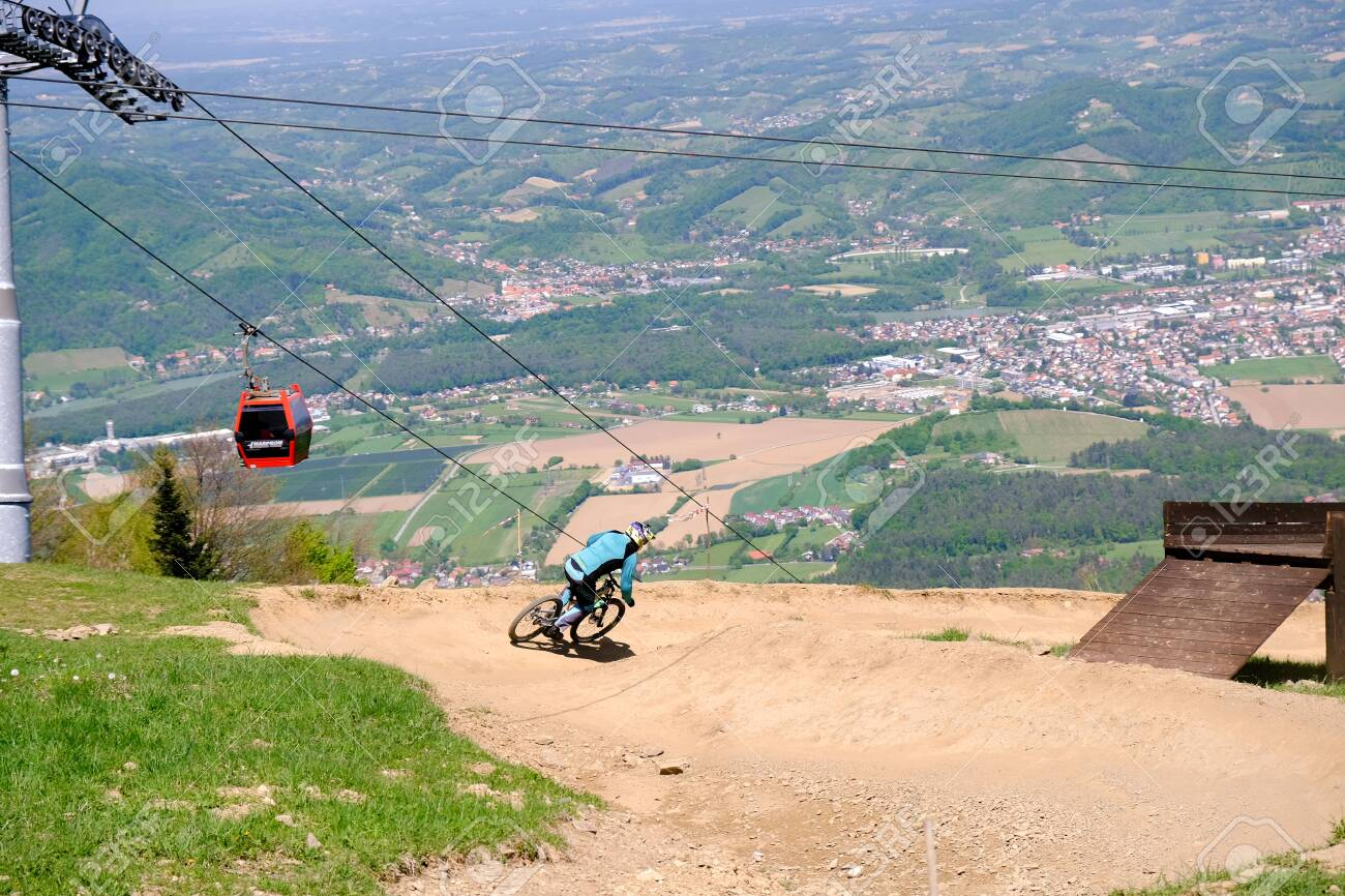 Maribor, Slovenia - May 2, 2019: Downhill mountain bikers riding down the trail on Pohorje near Maribor, Slovenia. Pohorje bike park is very popular with riders. - 137010541