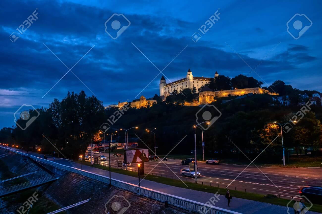 Bratislava, Slovakia - Sept 24 2019: Bratislava castle illuminated in evening glow against dramatic sky, moody and romantic scene of landmark in Slovak capital - 137011830