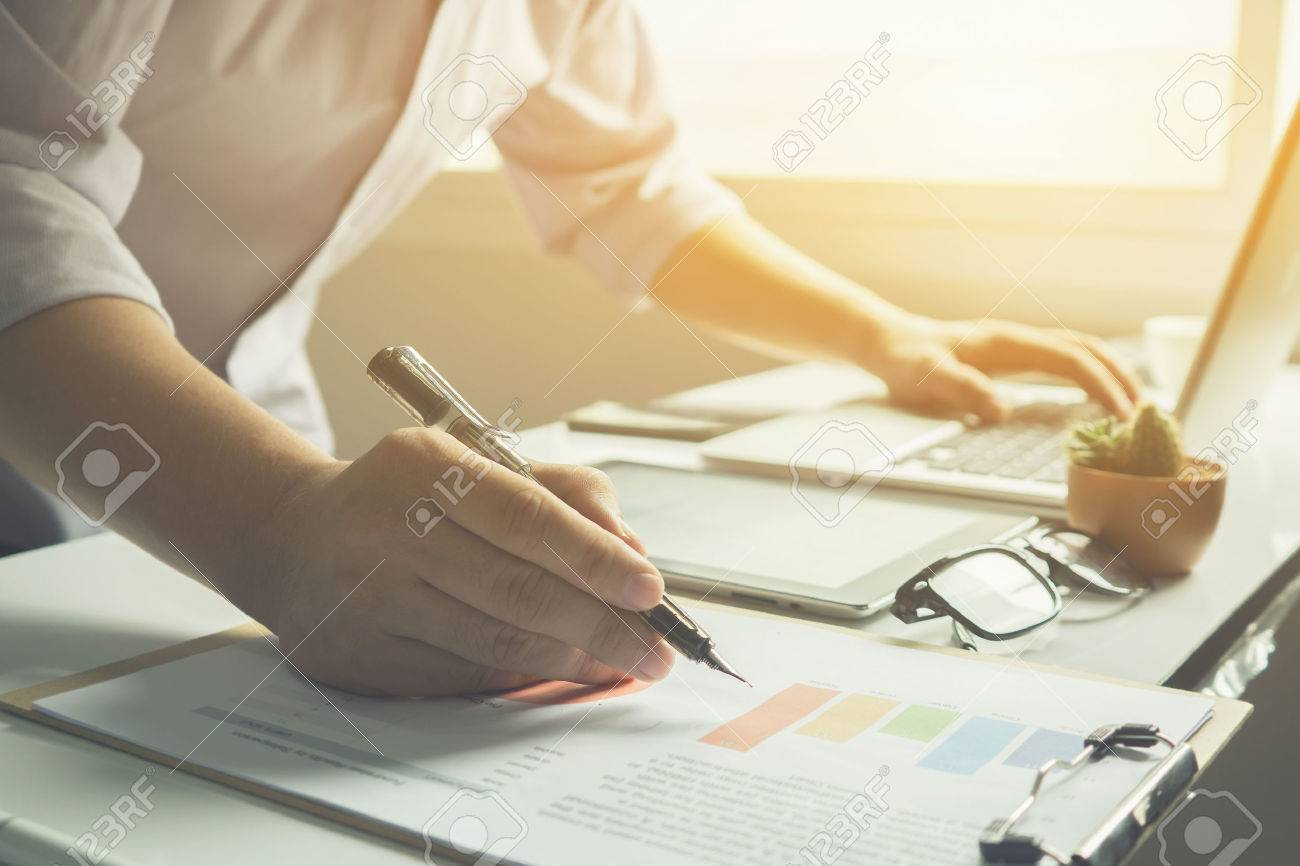 Business man working at office with laptop and documents on his desk, consultant lawyer concept,young male student typing and writing on business chart sitting at wooden table,vintage color - 66407617