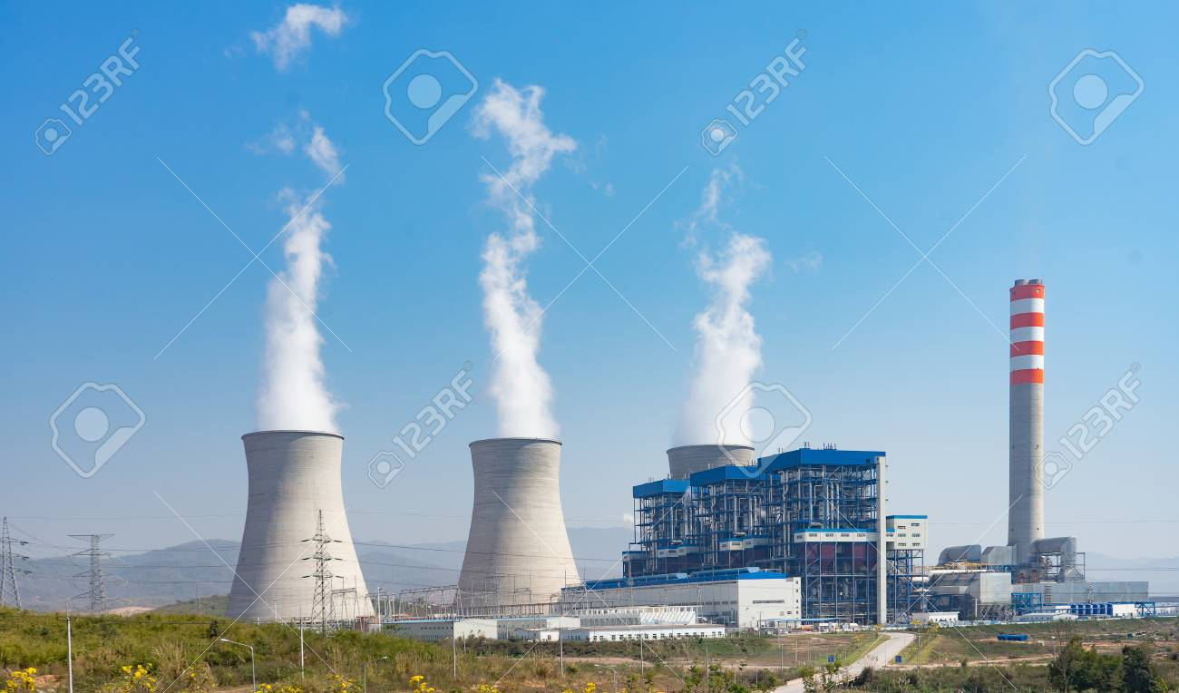 A coal-fired power station in the distance in agricultural landscape