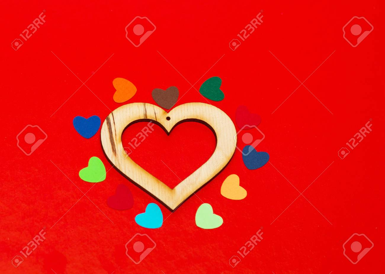 multicolored paper hearths around a wooden  heart  on red paper Stock Photo - 17024524