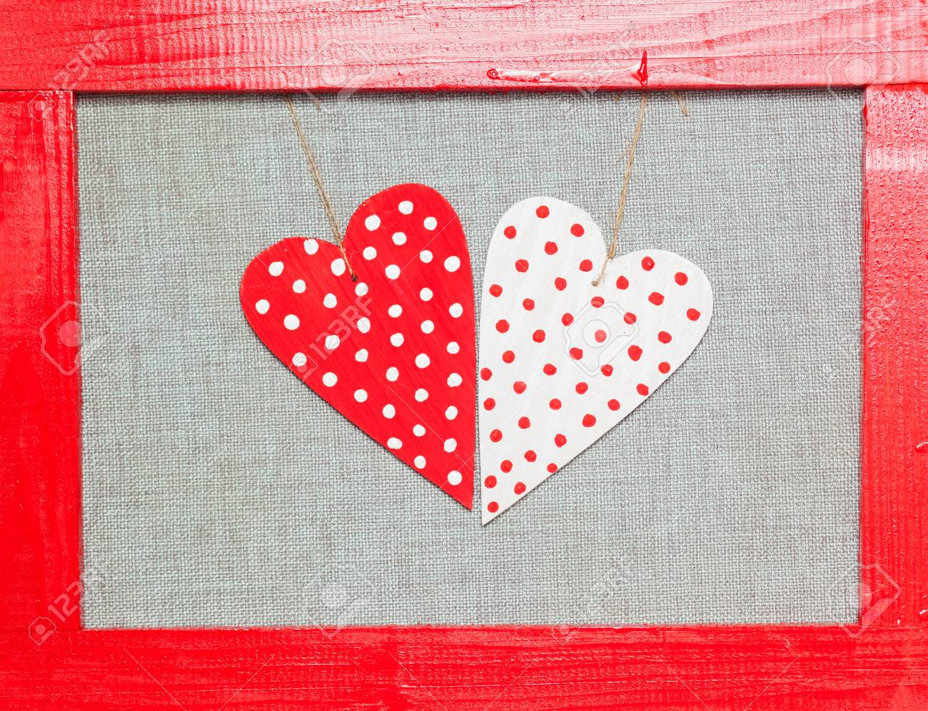 two wooden multicolored hearts in the red frame on grey background Stock Photo - 17174506