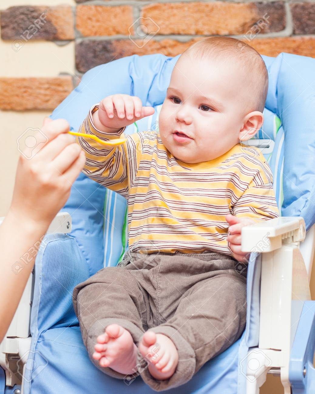 Baby is being fed by her mum sitting on   high chair Stock Photo - 17181990