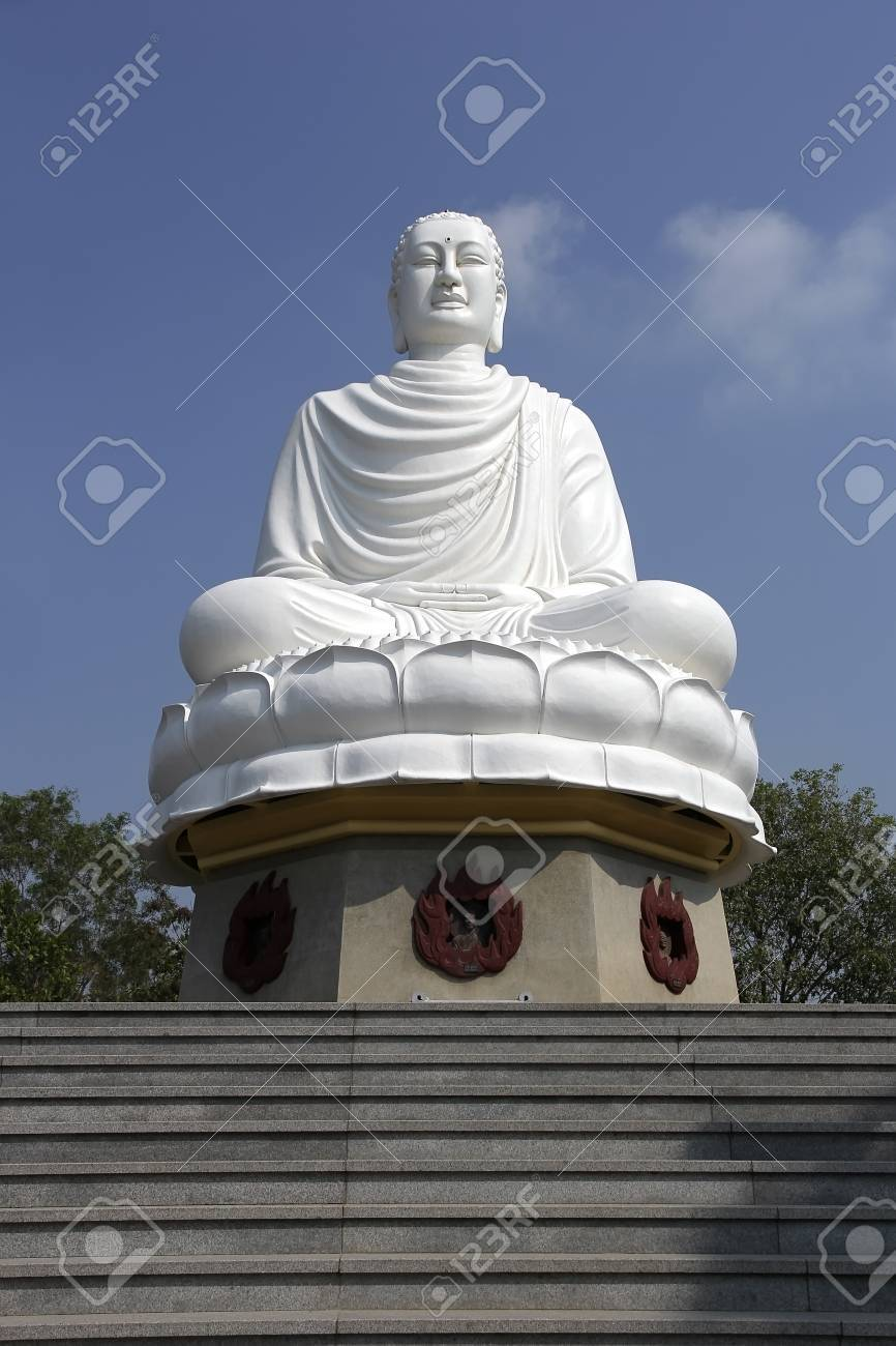 White Buddha Statue Sitting In Lotus Flower Against The Blue Stock