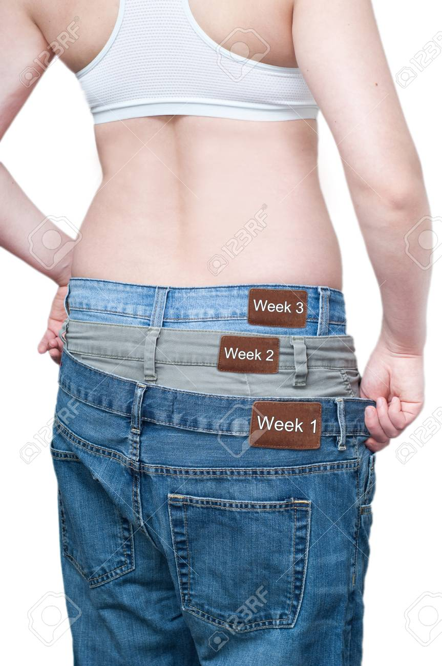 yuong woman monitoring weekly weight loss by wearing tree jeans