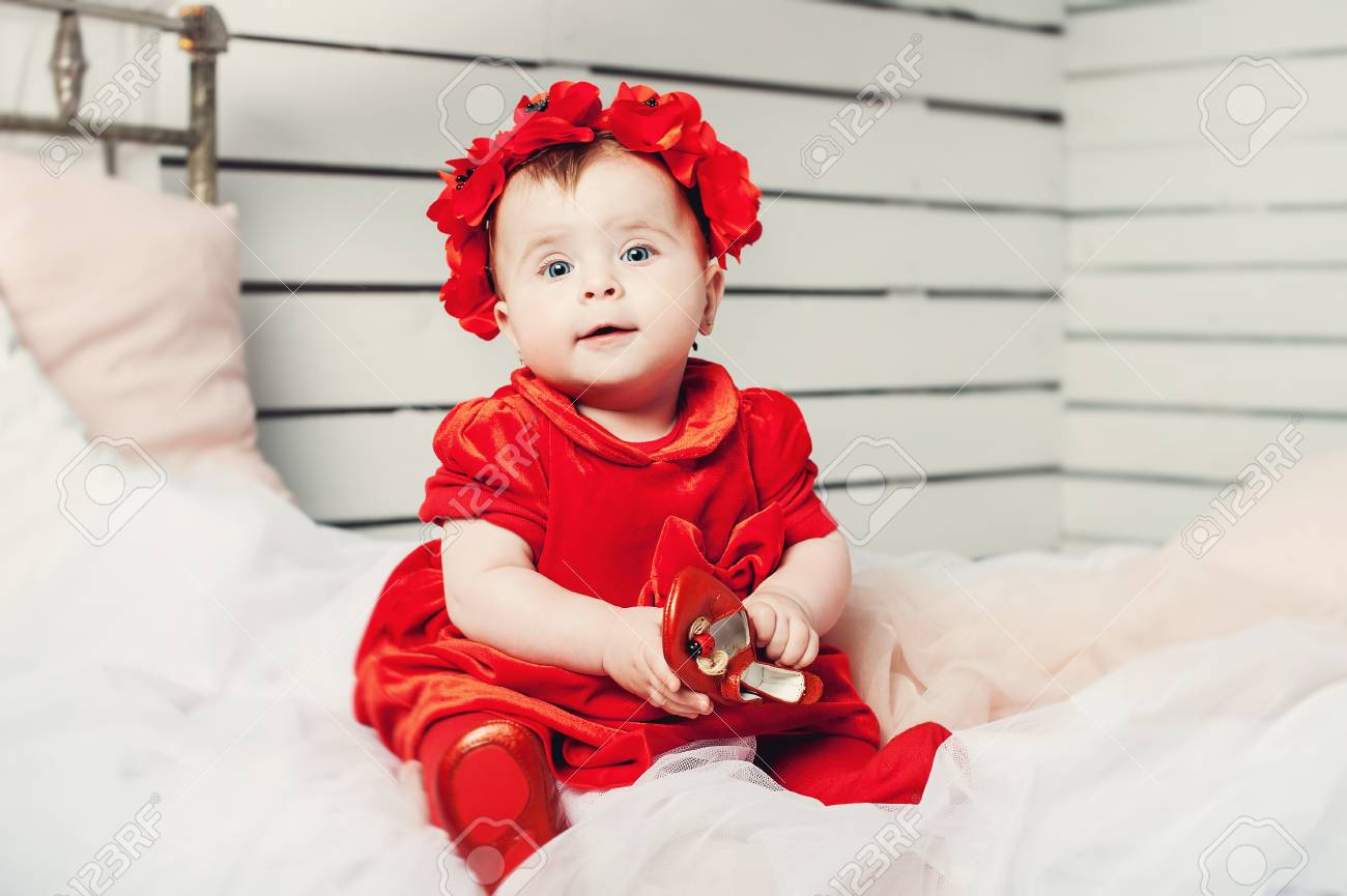 4846a132ec0d Cute Little Baby In A Red Dress And A Red Wreath On Her Head Stock ...