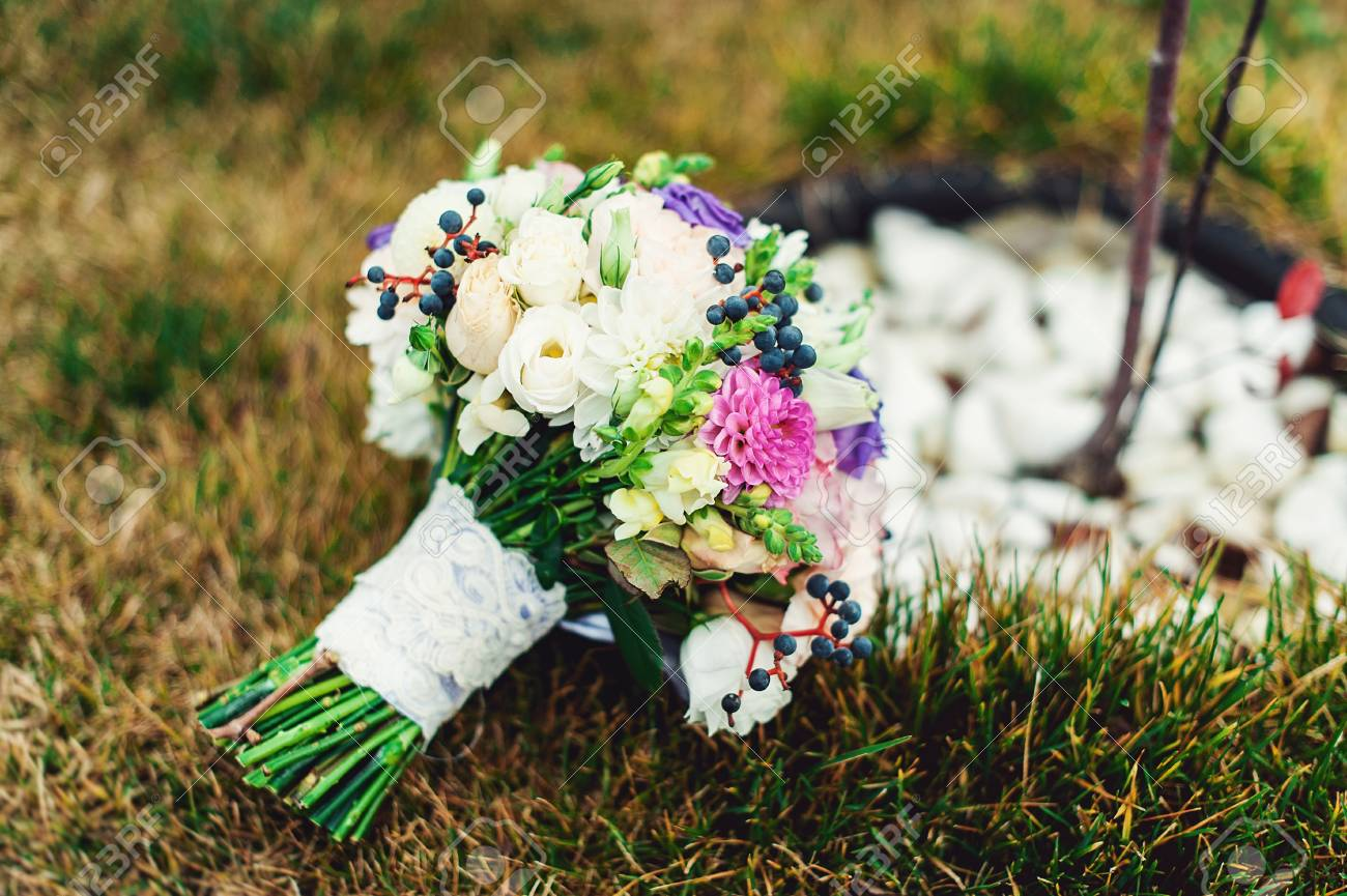 Bridal bouquet of different flowers wrapped lace ribbon on green bridal bouquet of different flowers wrapped lace ribbon on green grass stock photo 74183735 izmirmasajfo