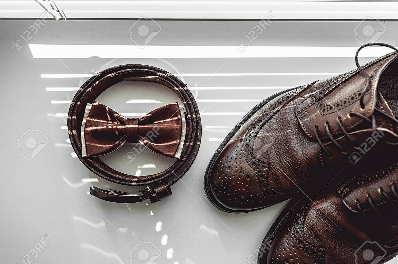c9179654be9e Brown bow tie, leather shoes and belt. Grooms wedding morning. Close up of