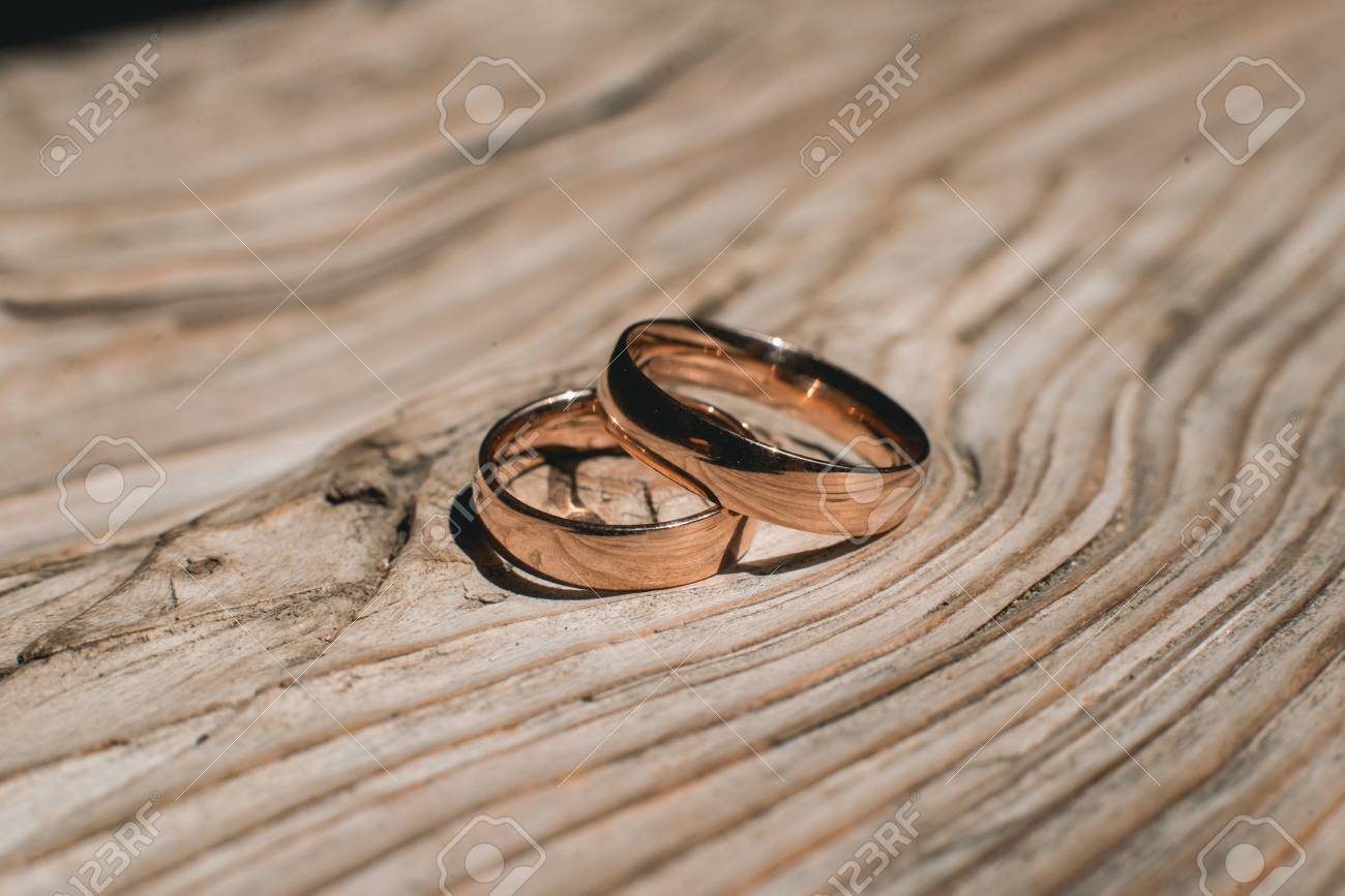 Pair Of Wedding Golden Rings On The Yellow Wooden Rustic Background Stock Photo