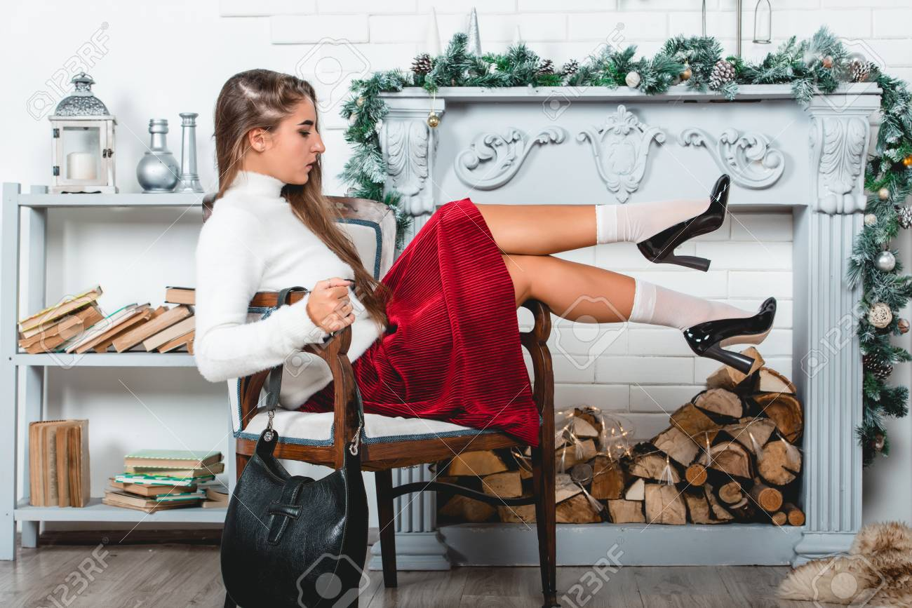 gorgeous young female in a red skirt and white pullover sitting in retro armchair on a christmas decorated wall background. Erotic legs in white socks and black varnish high heells - 112610699