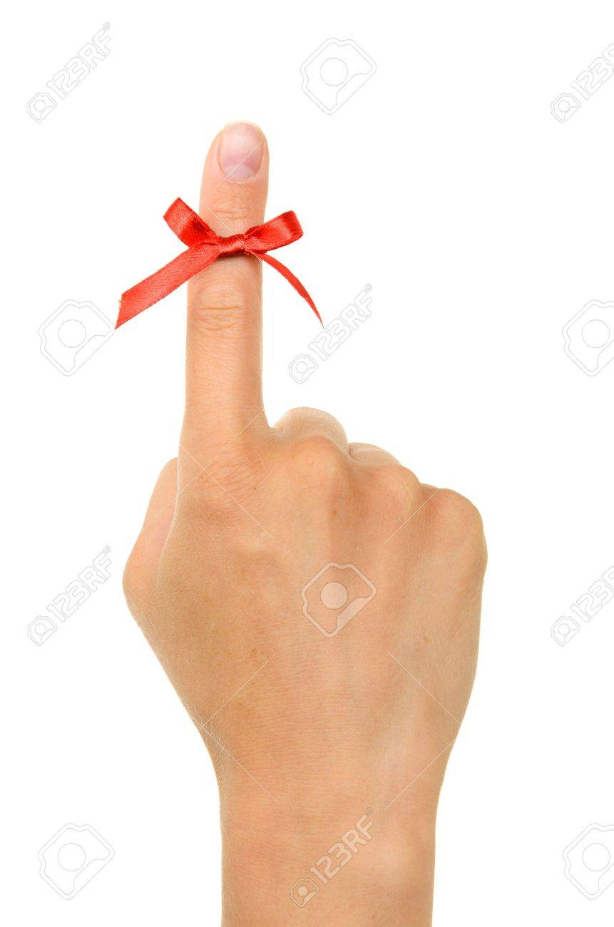 Red string tied around finger as a reminder, isolated on white background. - 13944933