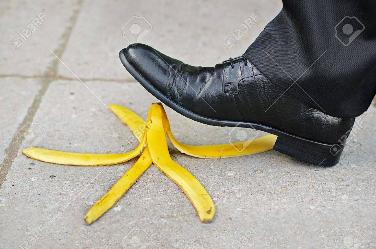 Businessman about to slip and fall on a banana skin Stock Photo - 13944943