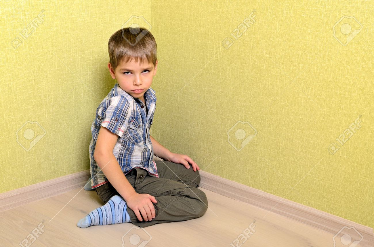 Angry and sad boy sitting in corner Stock Photo - 16826603