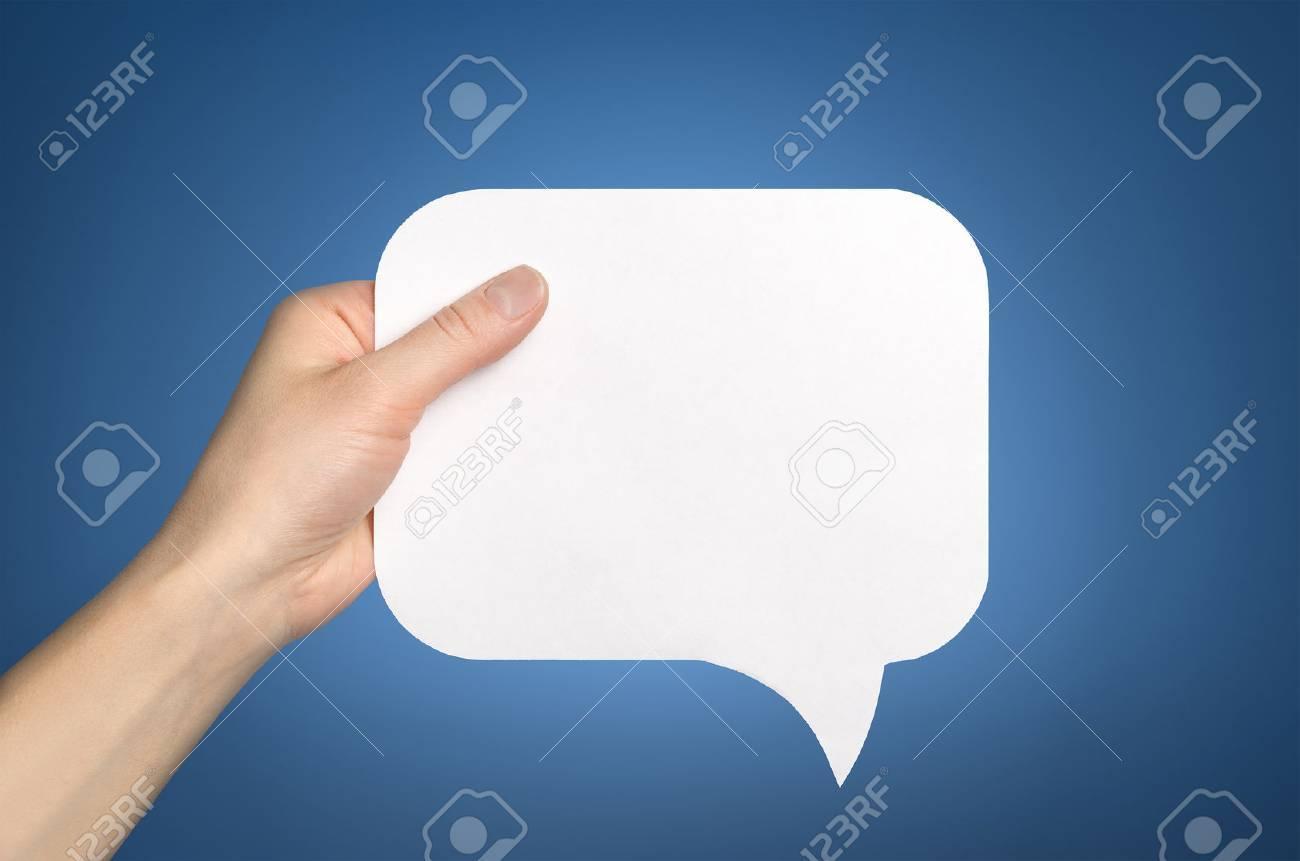 Hand holding an empty speech bubble on blue - 29100114