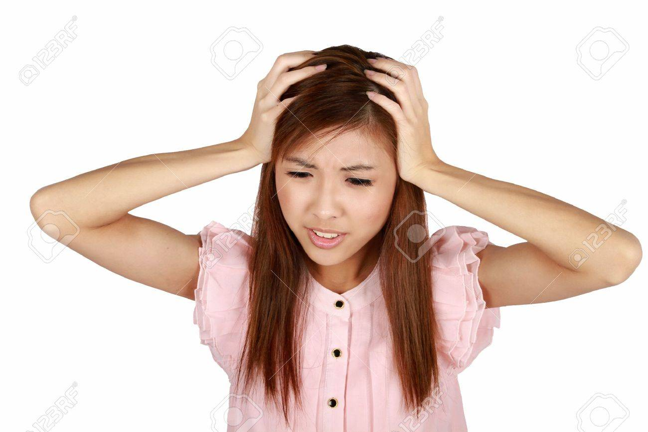 Young asian woman having a headache. Isolated on a white background. Stock Photo - 9689649