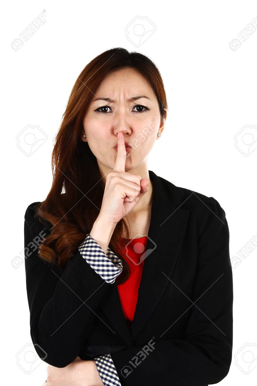 Portrait of young Asian business woman keeping finger on her lips and asking to keep quiet, isolated on white background Stock Photo - 22472346