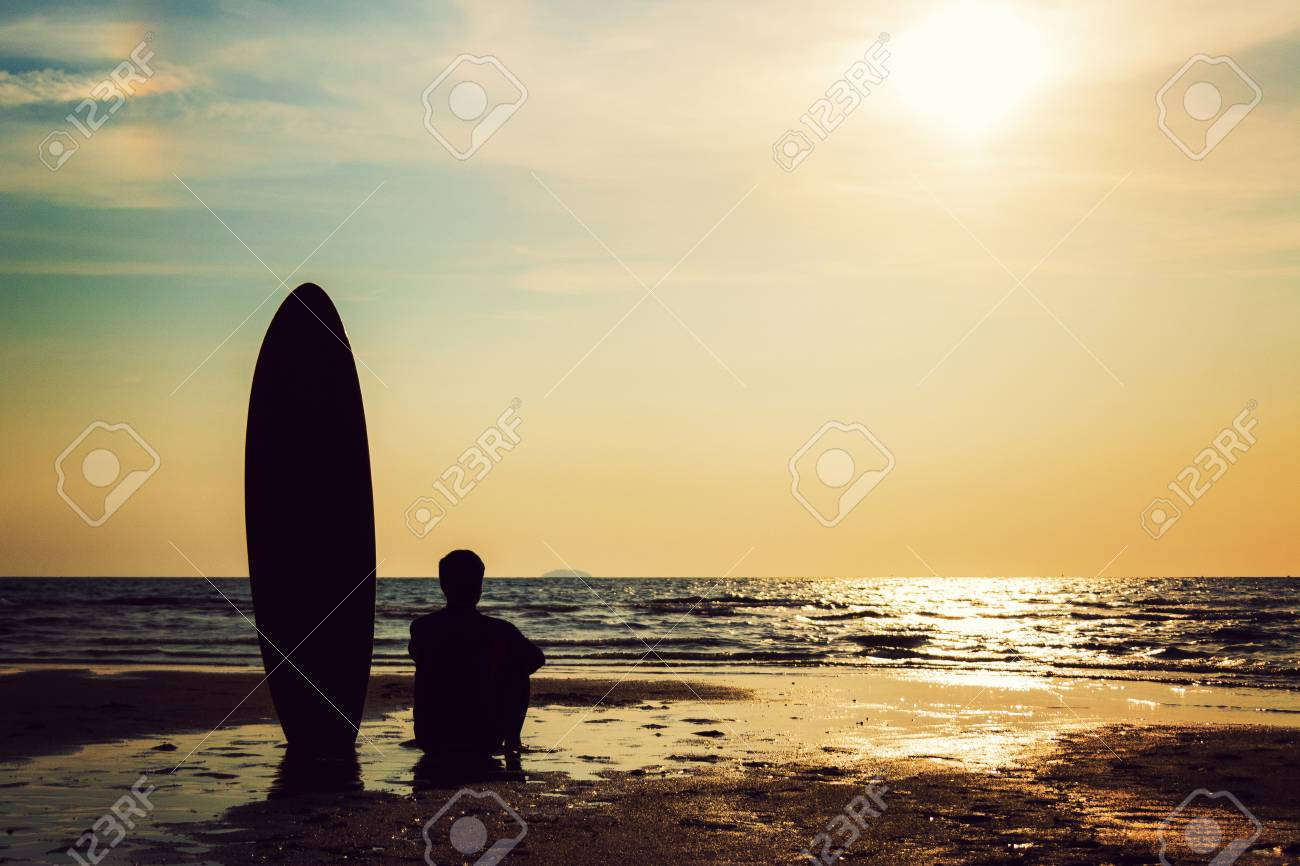 Silhouette Of Surf Man Sitting With A Surfboard On The Seashore