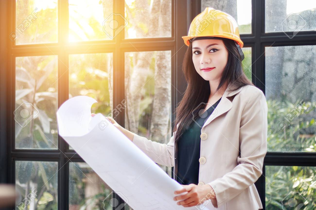 Portrait Of Beautiful Asian Woman Architect Builder With Yellow Helmet Hard  Hat Studying Blueprint Plan Of