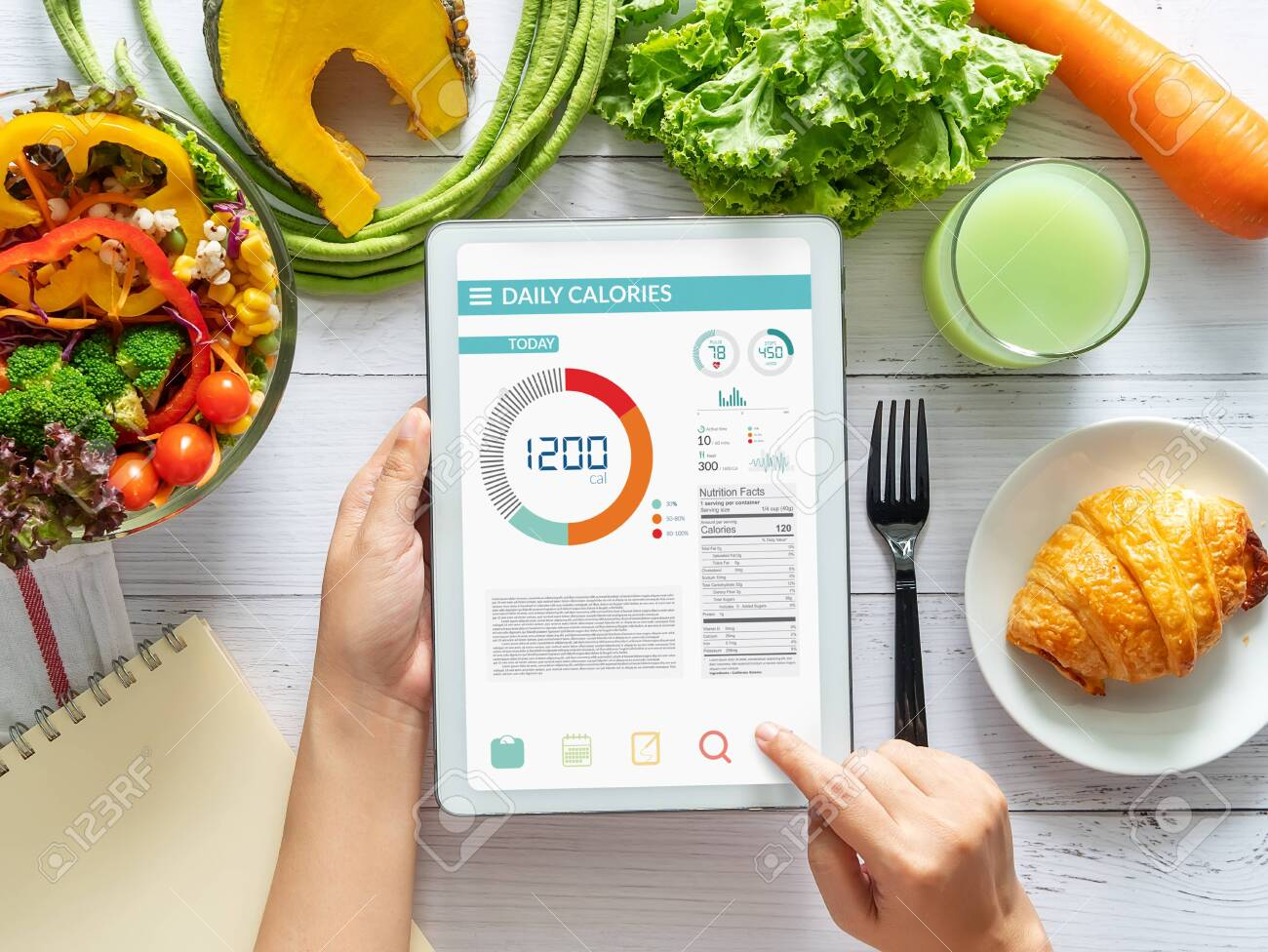 Calories counting , diet , food control and weight loss concept. woman using Calorie counter application on tablet at dining table with fresh vegetable salad - 129973977