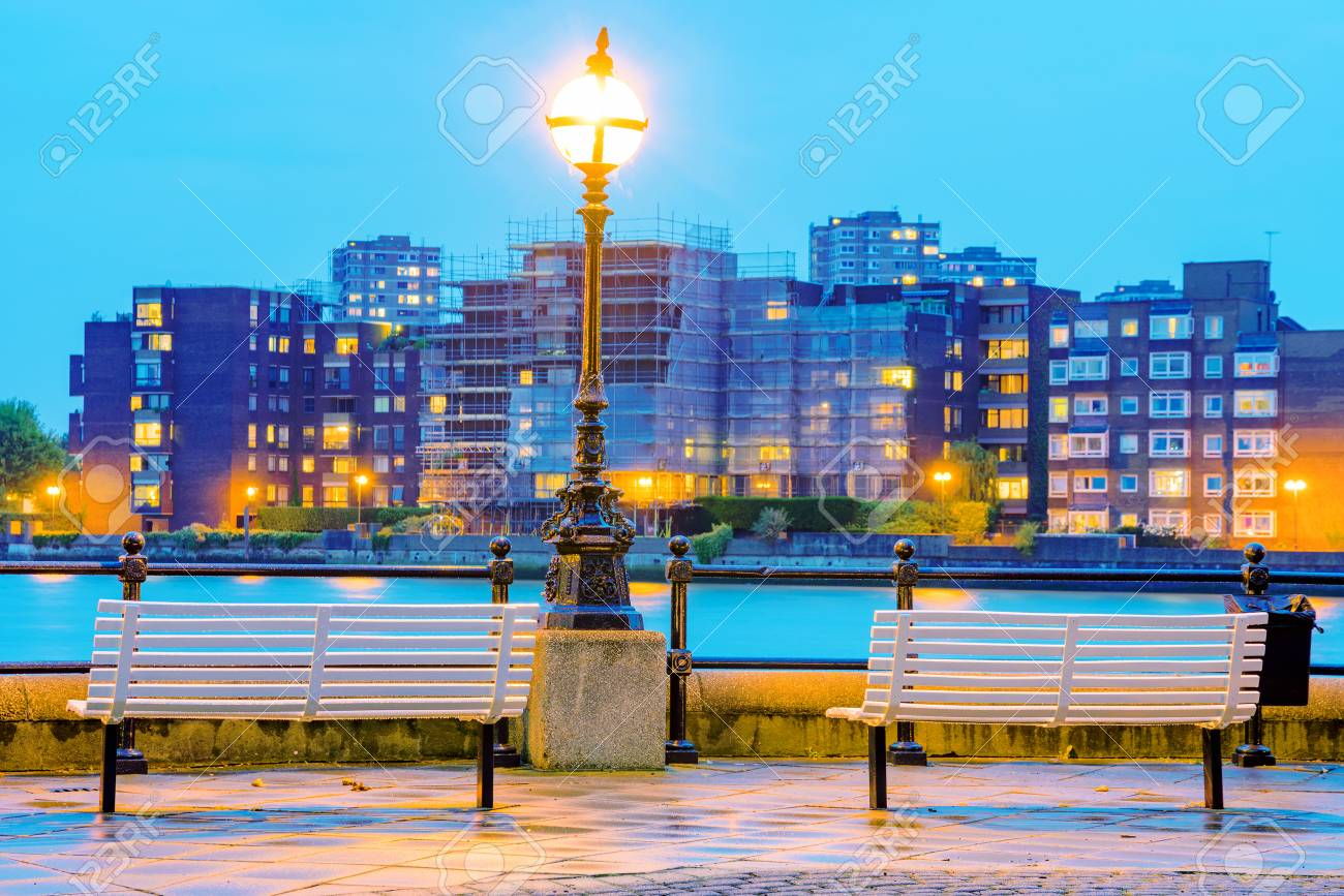 Riverside benches at night with out of focus buildings in the