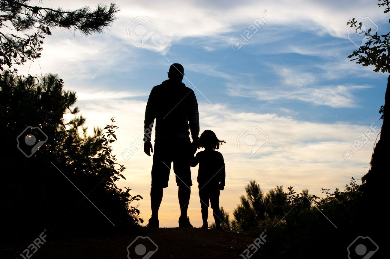 Silhouette of father and daughter holding hands watching the sunset on the top of a forest path Stock Photo - 15073281