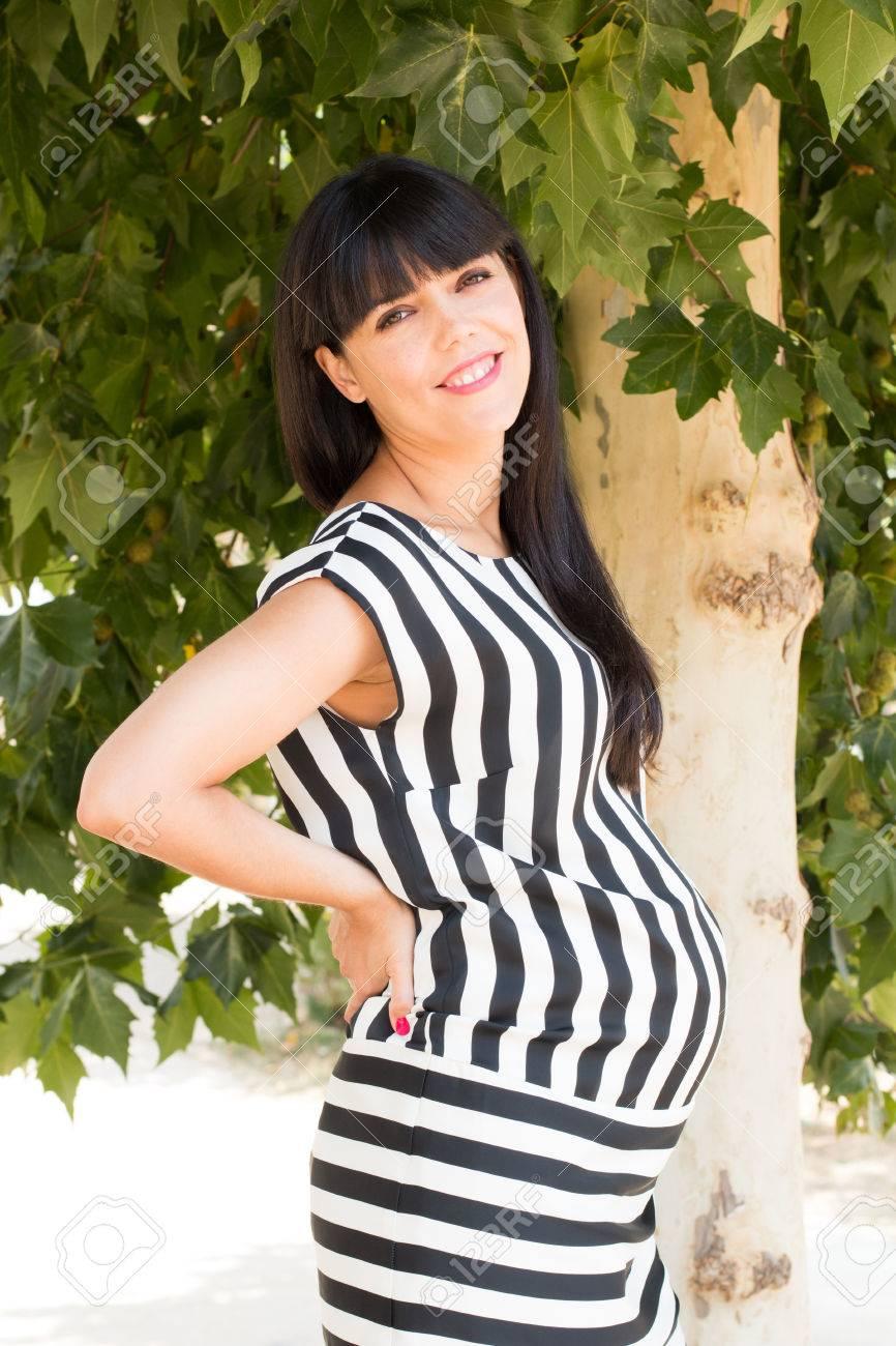 e082bf899 Foto de archivo - Mujer embarazada con estilo y hermosa en un vestido de  rayas blancas y negras debajo de un árbol