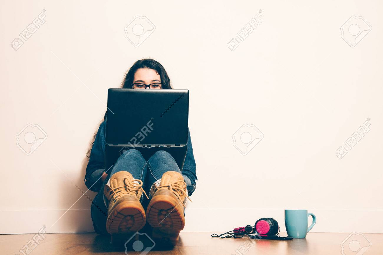 Girl sitting on the floor with a laptop looking at screen concentrated. Filter effect added. - 37880727