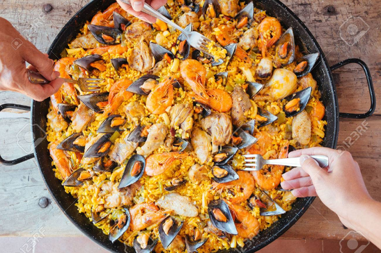 Mixed paella and hands with forks taking rice. Aerial view. - 40912797
