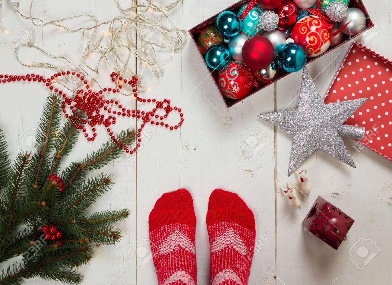 Como Decorar Calcetines Para Navidad.Pies De Una Persona Con Calcetines Rojos Listo Para Decorar El Arbol De Navidad Rodeado De Varios Adornos En El Suelo