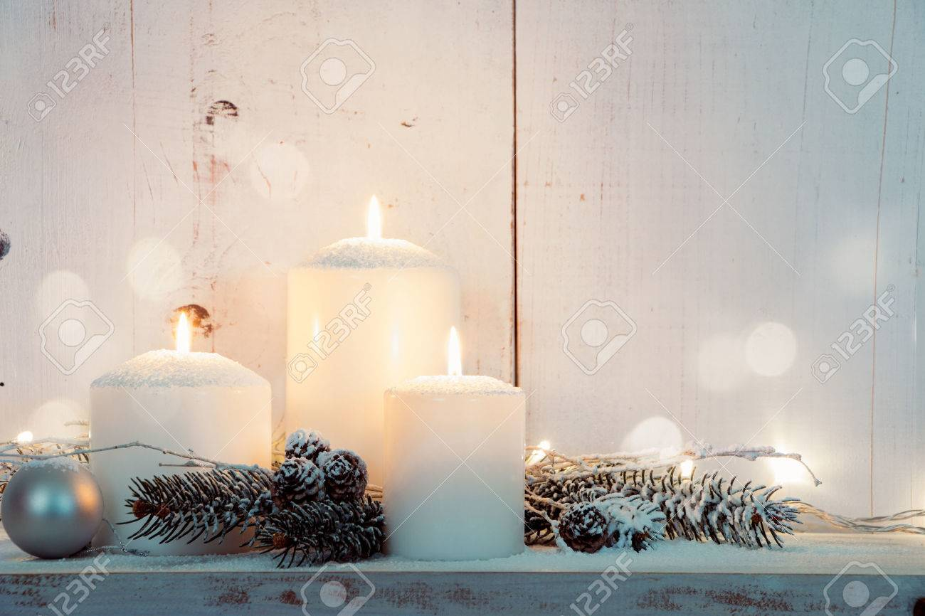 Christmas candles and snowy fir branches over white wooden background with lights - 46562452