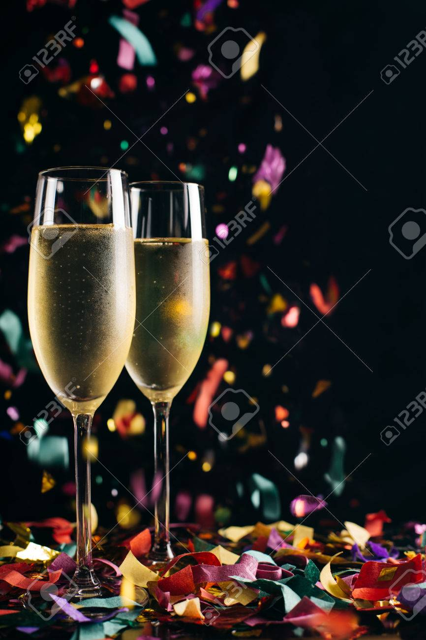 Two bright icy champagne glasses and confetti falling - 47071058